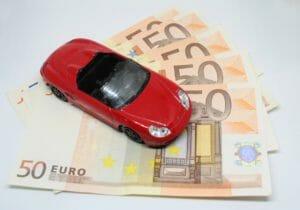 50ユーロ札が5枚扇状に並んでその上に赤いスポーツカーの模型が置いてある