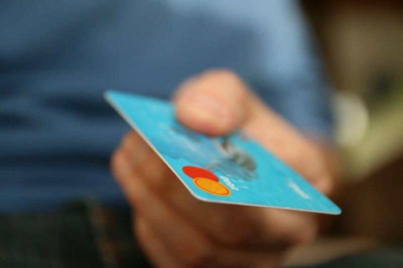 水色のクレジットカードを差し出す男性の右手