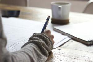 机の上の書類にペンで書き込みする右腕